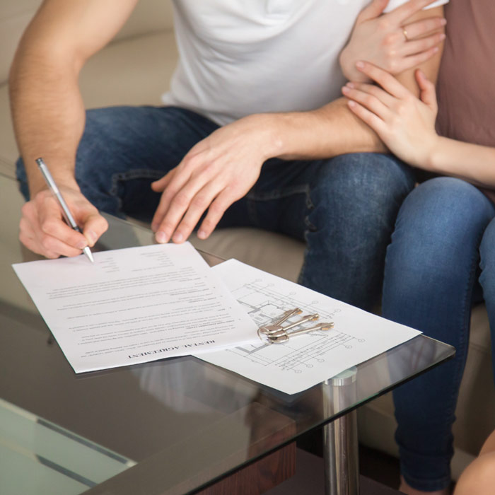 Young couple signing buy to let agreement